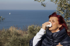 Woman sneezing, blowing nose into tissue above sea coast Royalty Free Stock Image