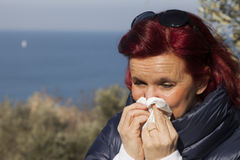 Woman sneezing, blowing nose into tissue above sea coast Stock Photo