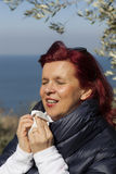 Woman sneezing, blowing nose into tissue above sea coast Royalty Free Stock Photography