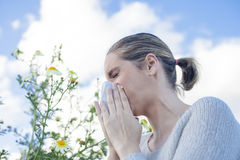 Woman sneezing in a daisy flowers meadow Stock Photo