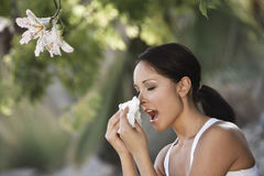 Woman Sneezing By Flowers. Closeup side view of a young woman sneezing by flowers Stock Photo