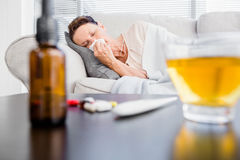 Woman sneezing with herbal tea and medicine on foreground Stock Photo