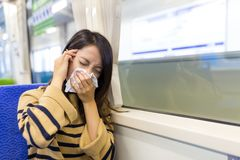 Woman sneezing inside train compartment Royalty Free Stock Image