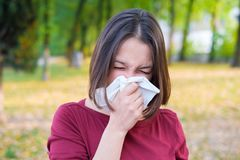 Woman sneezing in a kleenex because of cold and flu. Woman sneezing in a kleenex because of seasonal allergy Royalty Free Stock Images