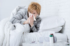 Woman with sneezing nose blowing in tissue on bed suffering cold flu virus symptoms having medicines tablets pills. Young sick woman with sneezing nose blowing Royalty Free Stock Image