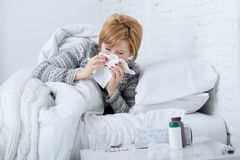Woman with sneezing nose blowing in tissue on bed suffering cold flu virus symptoms having medicines tablets pills. Young sick woman with sneezing nose blowing Stock Photography