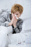 Woman with sneezing nose blowing in tissue on bed suffering cold flu virus symptoms having medicines tablets pills Stock Image