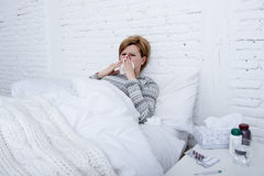 Woman with sneezing nose blowing in tissue on bed suffering cold flu virus symptoms having medicines tablets pills Royalty Free Stock Images