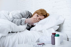 Woman with sneezing nose blowing in tissue on bed suffering cold flu virus symptoms having medicines tablets pills Royalty Free Stock Photography