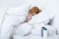 woman with sneezing nose blowing in tissue on bed suffering cold flu virus symptoms having medicines tablets pills Stock Photos