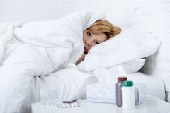 Woman with sneezing nose using tissue on bed suffering cold flu virus having medicines. Young sick woman with sneezing nose using tissues lying on bed suffering Stock Photos