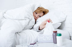 woman with sneezing nose using tissue on bed suffering cold flu virus having medicines Royalty Free Stock Photos