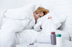 woman with sneezing nose using tissue on bed suffering cold flu virus having medicines Royalty Free Stock Photography