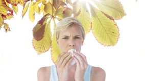 Woman sneezing while suffering from allergy against autumn leaves. Digital composite video of woman sneezing while suffering from allergy against autumn leaves stock video footage