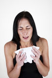 Woman sneezing into a tissue Stock Photography