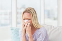 Woman sneezing in tissue Royalty Free Stock Photography