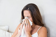 Woman sneezing with tissue on mouth. Pregnant woman sneezing with tissue on mouth in bedroom Royalty Free Stock Photography