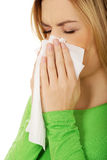 Woman sneezing to tissue. Stock Images