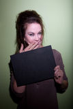 Woman snickering in mugshot. Woman with messy hair takes mugshot with blank board Stock Image
