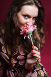 Woman sniffing a flower. Pretty woman sniffing a pink flower Royalty Free Stock Image
