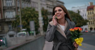 Woman sniffing flowers while speaking over the phone. Valentines day concept stock video