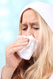 Woman with sniffles or sneezing. Woman wearing a hooded sweater holds a tissue due to sniffles or sneezing because of a cold or allergies Royalty Free Stock Photos