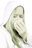 Woman with sniffles or sneezing. Woman wearing a hooded sweater holds a tissue due to sniffles or sneezing with high key green color effect Stock Images