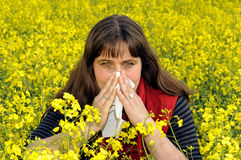 Woman sniffs. Woman with handkerchief in a field of stock photography