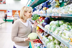 Woman sniffs broccoli and holds white cabbage in store Stock Photography