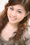 Woman sniling sweet. Sweet smiling woman with long brown curly hair Stock Photo
