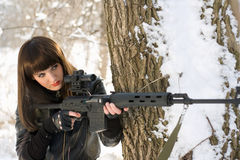 Woman with a sniper rifle. Portrait of beautiful young woman with a sniper rifle near the tree Stock Image
