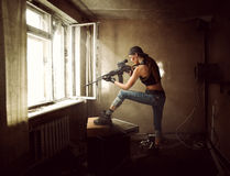 Woman sniper and Soldier aiming rifle at window. Young beautiful woman sniper and Soldier aiming a rifle at the window. She is in old room of abandoned building stock photography