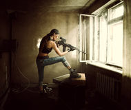 Woman sniper and Soldier aiming rifle at window. Young beautiful woman sniper and Soldier aiming a rifle at the window. She is in old room of abandoned building Royalty Free Stock Image