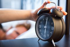 Woman Snoozes Alarm Clock in the Morning royalty free stock photos