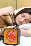 Woman snoozing a red alarm clock. Young woman snoozing a red alarm clock Stock Images