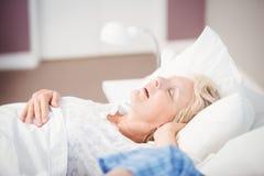 Woman snoring on bed next to husband. Senior women snoring next to husband on bed at home Stock Photo