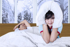 Woman and snoring man on bed. Young women sitting on bed and closed her ears after hearing her boyfriend snoring Stock Photography