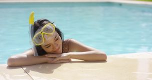 Woman in snorkel and goggles rests by pool stock video