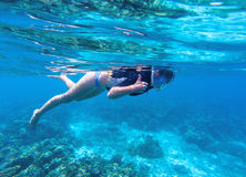 Woman snorkeling in blue water. Snorkel shows thumb in full face mask. Royalty Free Stock Images