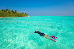 Woman snorkeling in clear tropical waters in front of exotic isl Stock Photography