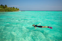 Woman snorkeling in clear tropical waters in front of exotic isl Royalty Free Stock Photos