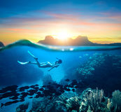 Woman snorkeling in clear tropical waters ocean on sunset day. Young woman snorkeling near the coral reef in the tropical Caribian sea on sunset day Stock Photo