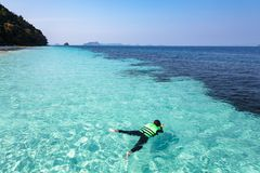 Woman snorkeling in crystal clear water, Andaman sea. Man snorkeling in crystal clear water, Andaman sea, Thailand Royalty Free Stock Photography