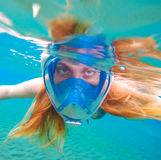 Woman snorkeling in full face mask. Female snorkel in clean turquoise sea. Royalty Free Stock Image
