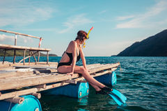 Woman in snorkeling gear on raft. A young woman wearing flippers and snorkeling mask is sitting on a raft in a tropical location Royalty Free Stock Photography