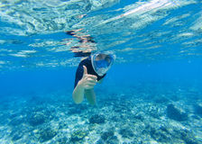 Woman snorkeling in shallow sea water. Snorkel shows thumb in full face mask. Stock Photos