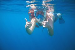 Woman snorkeling showing thumbs. Snorkel in full face mask. Female swim with loose red hair. Stock Photos
