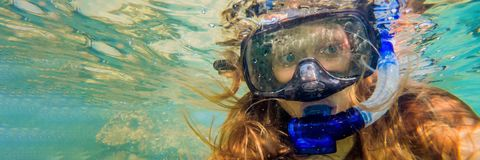 Woman snorkeling in tropical waters in front of exotic island BANNER, long format stock photography