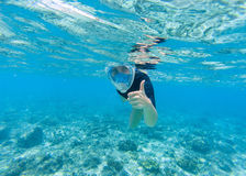 Woman snorkeling in turquoise sea water. Snorkel shows thumb in full face mask. Beautiful girl swims in sea. Underwater photo of oceanic landscape. Seaside Stock Images