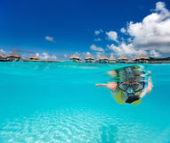 Woman snorkeling. Underwater photo of woman snorkeling in clear tropical waters in front of overwater villas Stock Photos